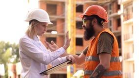 Byggmästare i skyddande hjälmar att diskutera på konstruktionsplatsen Byggmästare på konstruktionsplatsen Tekniker två har stock video