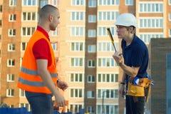 Byggmästare i spänning och konstruktörordförandearbetare med hjälmen och västen royaltyfri fotografi