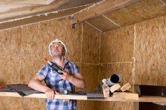Byggmästare med att dikta vapnet inom oavslutat hem royaltyfri fotografi