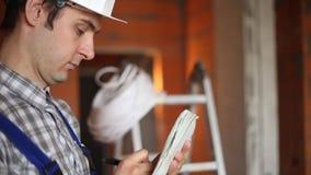 Byggmästare med en anteckningsbok på closeupen för konstruktionsplats lager videofilmer
