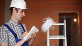 Byggmästare med en anteckningsbok på konstruktionsplatsen arkivfilmer