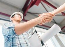 Byggmästare med ritningen som skakar partnerhanden