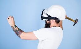 Byggmästare och renoveringbegrepp Hipster som är upptagen med renovering i virtuell verklighet Grabben med att bulta för HMD som  fotografering för bildbyråer