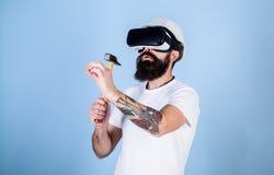 Byggmästare och renoveringbegrepp Man med skägget i VR-exponeringsglashåll hammare, ljus - blå bakgrund Grabb med att bulta för H royaltyfri foto