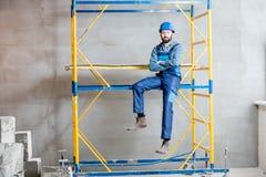 Byggmästare på materialet till byggnadsställning inomhus arkivbilder