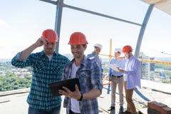 Byggmästare på platsen som arbetar med plan av konstruktionsprojektet på minnestavladatoren över Team Of Apprentices Holding Blue royaltyfria foton