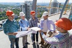 Byggmästare på platsen som ser på planritningleverantören som förklarar projekt till lärlinglaget arkivfoton