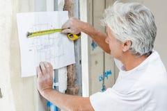 Byggmästare som använder måttband att kontrollera byggnadsplan Arkivbild