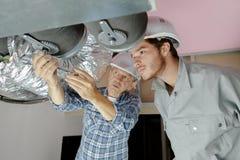 Byggmästare som arbetar på ventilationsrör arkivfoton