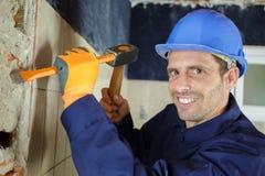 Byggmästare som bultar väggen royaltyfria bilder