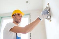 Byggmästare som inomhus arbetar med det malande hjälpmedlet arkivbilder
