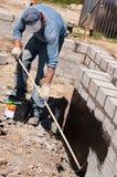 Byggmästare som isolerar fundament Arkivbilder