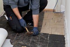 Byggmästare som lyfter gamla golvtegelplattor i en passage Royaltyfri Fotografi