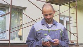 Byggmästare som räknar hans lönanseende på konstruktionsplatsen arkivfilmer