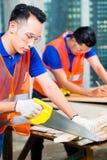 Byggmästare som sågar ett wood bräde av byggnads- eller konstruktionsplatsen Royaltyfri Fotografi
