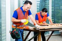 Byggmästare som sågar ett wood bräde av byggnads- eller konstruktionsplatsen Arkivbilder