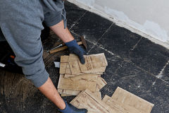 Byggmästare som tar bort skadade golvtegelplattor Arkivfoto