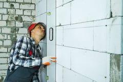 Byggmästare som trycker på bubblanivån för att blockera väggen som kontrollerar vertikalt dess kvalitet arkivbild