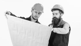 Byggmästare tekniker, arkitektarbete på platsen Män i hjälmar Royaltyfri Foto