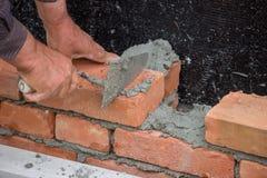 Byggmästarearbetare med väggen för murslevbyggnadstegelsten Arkivbild