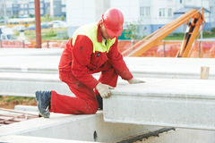 Byggmästarearbetare som installerar den konkreta slaben Arkivbild