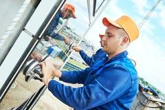 Byggmästarearbetare som installerar glass fönster på fasad Royaltyfri Foto