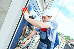 Byggmästarearbetare som installerar glass fönster på fasad Arkivbilder