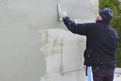 Byggmästarearbetare som rappar fasaden Royaltyfri Bild