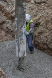 Byggmästarearbetare som siktar och förlägger betong 2 arkivfoto