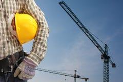 Byggmästarearbetaren i enhetligt och hjälmen som fungerar med, står hög kranen Arkivfoton