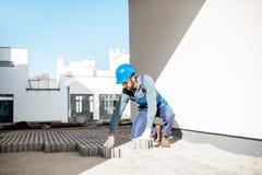 Byggmästarebeslag som stenlägger tegelplattor royaltyfri bild