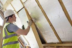 ByggmästareFitting Insulation Into tak av det nya hemmet Arkivfoto