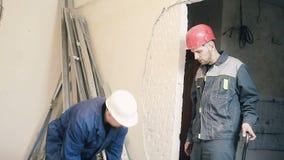 Byggmästaren förstör murbruken på väggen stock video