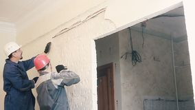 Byggmästaren förstör murbruken på väggen arkivfilmer
