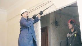 Byggmästaren förstör murbruken på väggen lager videofilmer