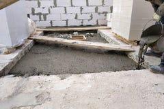 Byggmästaren häller en cementmorteltjock skiva mellan golven av huset genom att använda en hink royaltyfri fotografi
