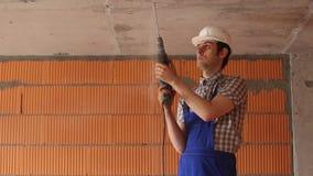 Byggmästaren i en hjälm borrar taket arkivfilmer