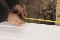 Byggmästaren i handskar mäter längden av en metallprofil med en måttband royaltyfri foto
