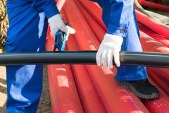 Byggmästaren klipper av ett stycke av det svarta röret över röda stora plast- rör royaltyfria bilder