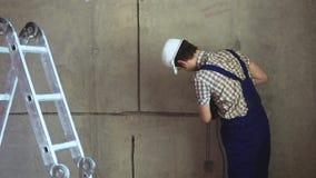 Byggmästaren med hjälpmedlet utför reparationsarbete arkivfilmer