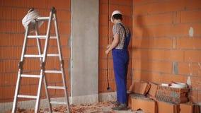 Byggmästaren utför reparationerna arkivfilmer