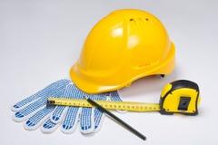 Byggmästares hjälpmedel - hjälmen, arbetshandskar, pennan och måttet tejpar ove Arkivbild