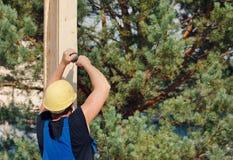 Byggmästare eller snickare som borrar ett hål Arkivbild