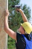 Byggmästare eller snickare som borrar ett hål Arkivbilder