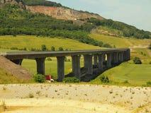 Byggnad av den nya huvudvägbron Konkreta pelare ovanför den lilla dalen, stor kulle med minen i bakgrund Arkivfoton