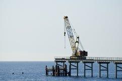 Byggnad av en havsbro med tungt maskineri royaltyfria bilder