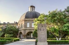 Byggnad av Gevorgyan den andliga akademin med det forntida khachkar Royaltyfri Fotografi