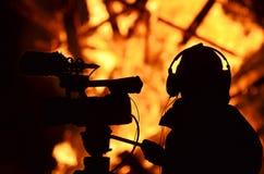 Byggnad för filmande för kameramanreporterjournalisten på brand flammar royaltyfri bild