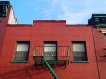 Byggnad för röd tegelsten med den gröna brandflykten i kineskvarteret New York City royaltyfria foton