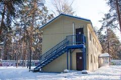 Byggnad i en rekreationmitt i vinterpinjeskogen Arkivfoto